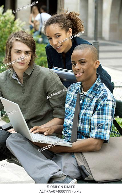 University students studying on campus with laptop computer, portrait