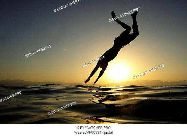 Man jumping into the sea at sunset