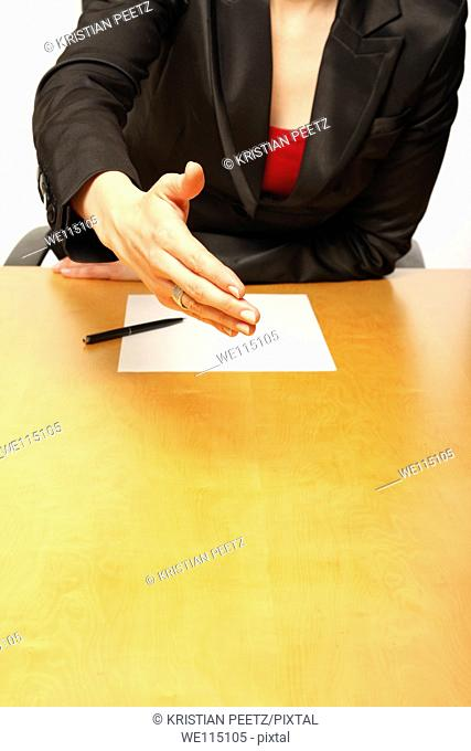 View of a business-woman sitting at a desk greeting with a blank paper infront