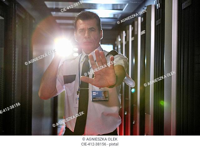 Portrait male security guard with flashlight gesturing stop in server room