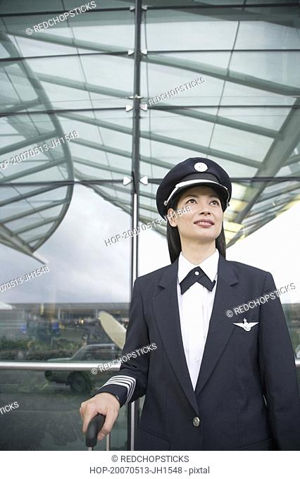 Close-up of a female pilot standing at an airport