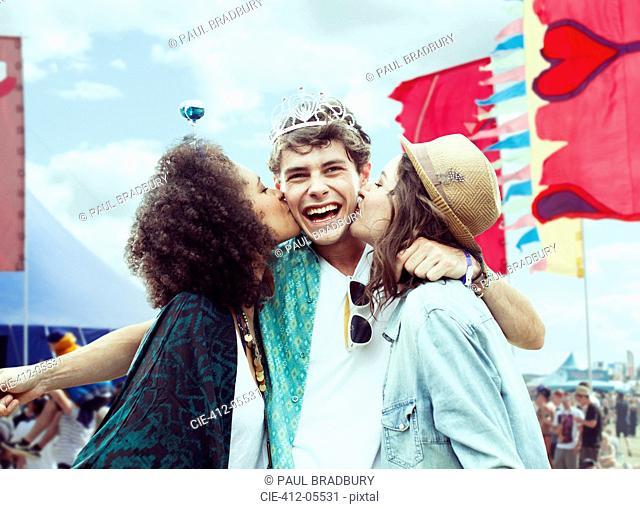 Women kissing manÍs cheek at music festival
