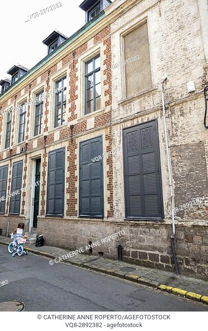 Little girl cycling with her dolly past traditional shuttered frontage in old Valenciennes historic city centre, France