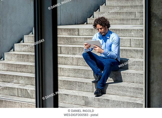 Businessman sitting on stairs looking at tablet