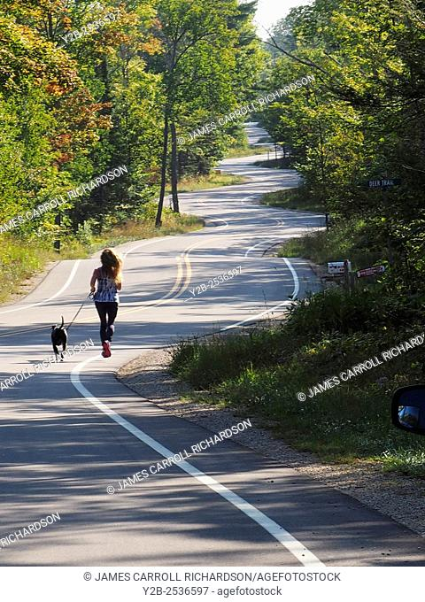 Wisconsin Door County Elison Bay Windy Road with female runner and dog