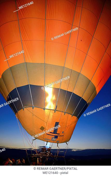 Propane heater inflating a hot air balloon at dawn with Urgup city lights Cappadocia Turkey