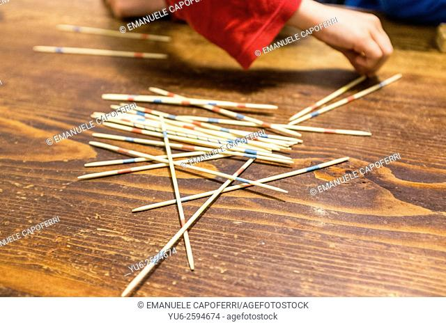 Children playing mikado on the table of the house