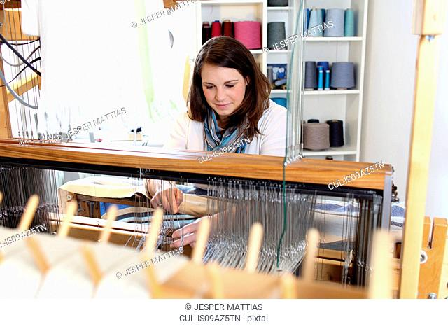 Young woman using loom