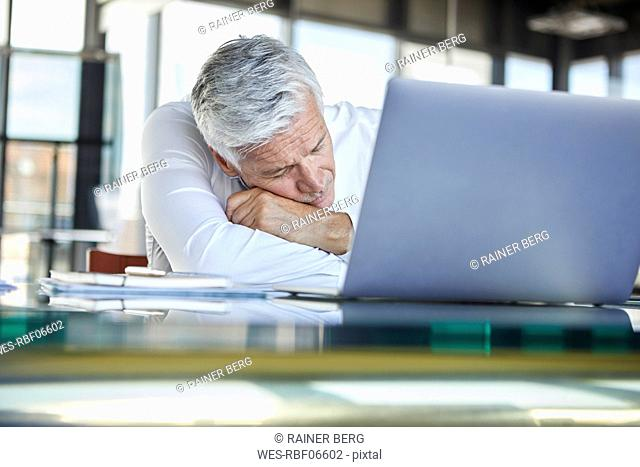 Exhausted businessman sleeping in front of laptop