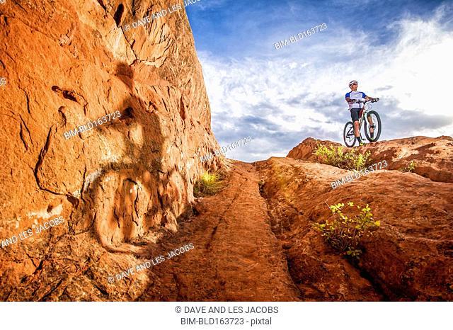 Caucasian man riding mountain bike on mountain