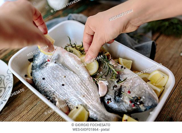 Woman preparing Sea Bream in baking dish with fresh lemon, rosemary and pepper