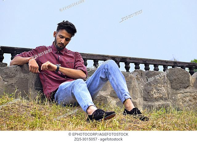 Young man with checked shirt looking at his watch, Pune, Maharashtra