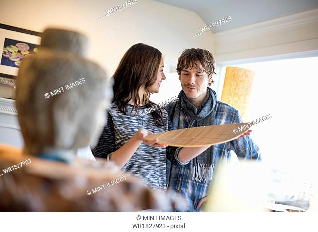 Smiling couple standing in a living room, woman holding a wooden tray