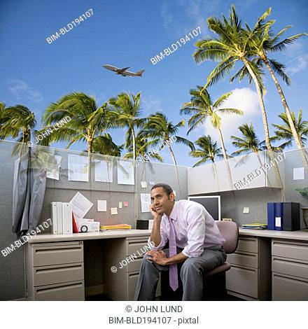 African American businessman daydreaming of vacation at desk
