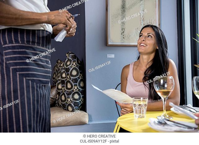 Woman speaking to waiter in restaurant