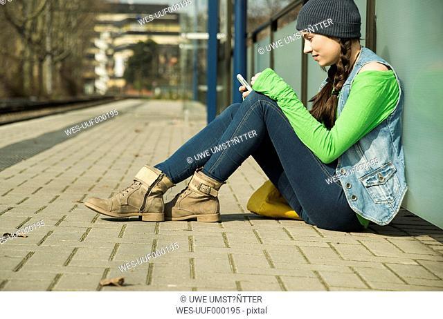 Teenage girl using smartphone at platform