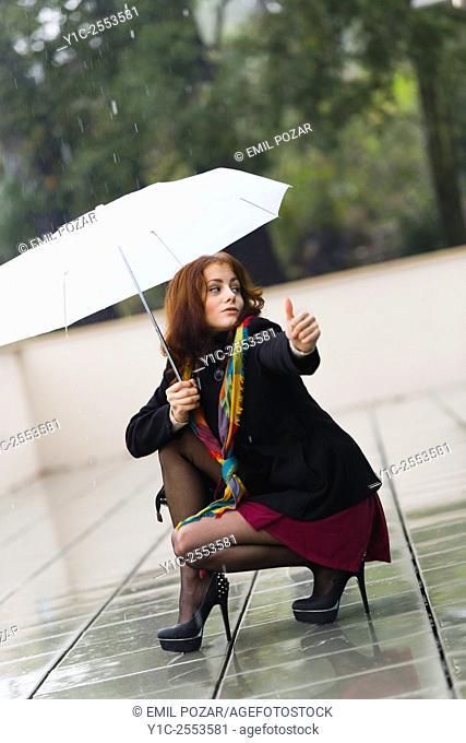 Teenager girl hitchhiking on rainy day