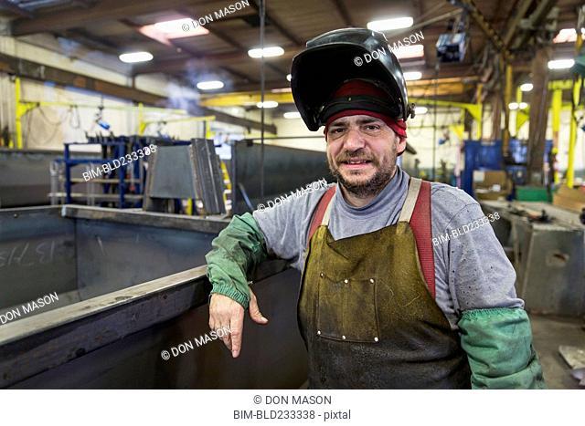 Caucasian welder posing in factory