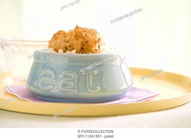 Minced turkey meatballs on brown rice in a bowl with the word 'eat' written on it