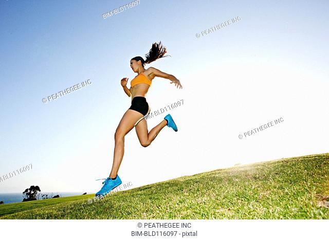 Hispanic woman running in rural landscape