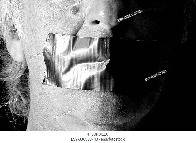 NOTE: Self portrait with proper release attached. A man's mouth is covered and taped closed with duct tape, side lit with half of face in shadow