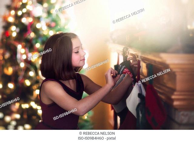 Young girl looking at christmas stocking