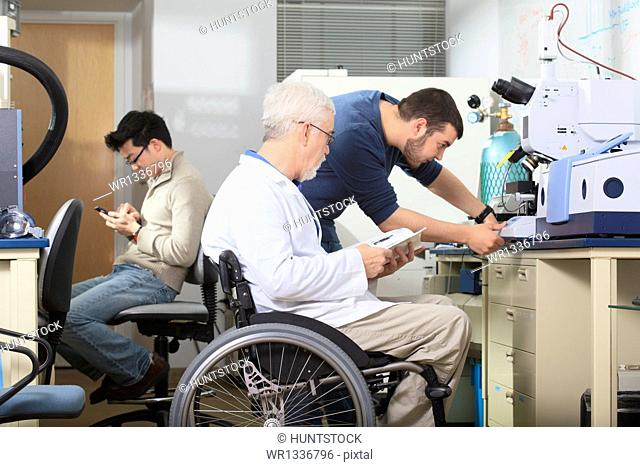Professor with muscular dystrophy and engineering student using manual to adjust x-ray fluorescence analyzer in a laboratory