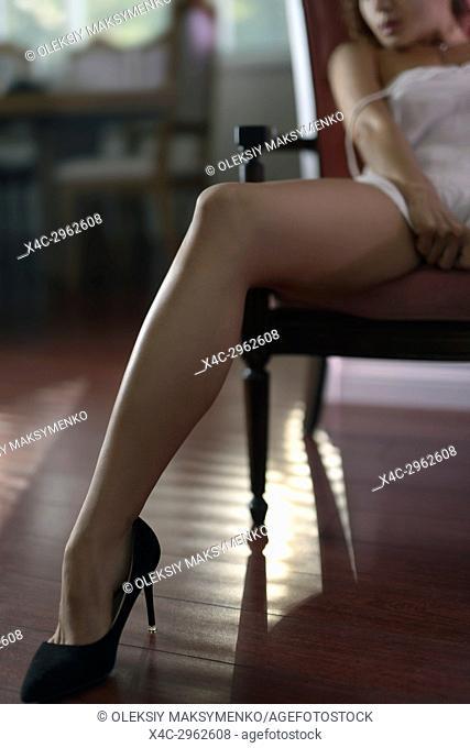 Sexy long legs in high heel shoes, sensual closeup of a woman sitting in a chair wearing a night shirt
