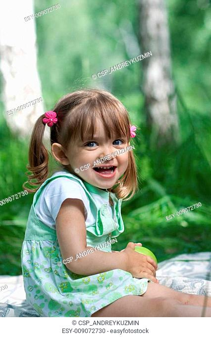 Little girl portrait with green apple in her hands outdoor