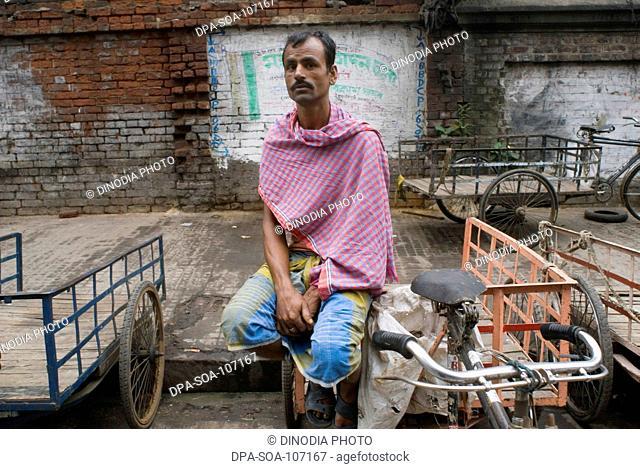 Cycle Rickshaw Rider on street waiting for passenger ; Kolkata ; West Bengal ; India