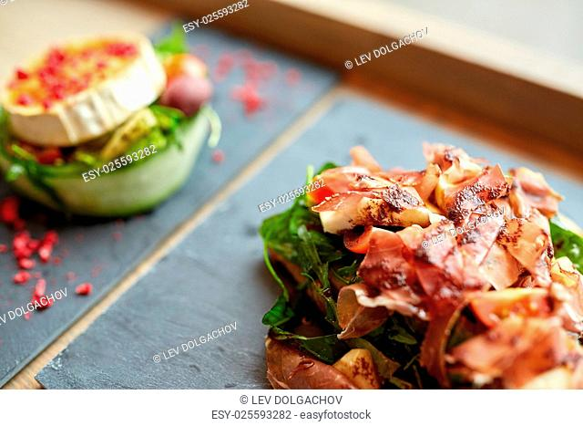 food, dinner, haute cuisine and eating concept - prosciutto ham and cheese salads on stone plates at restaurant