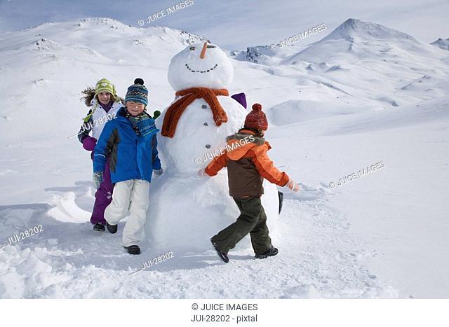 Boy and girls walking around snowman on winter day
