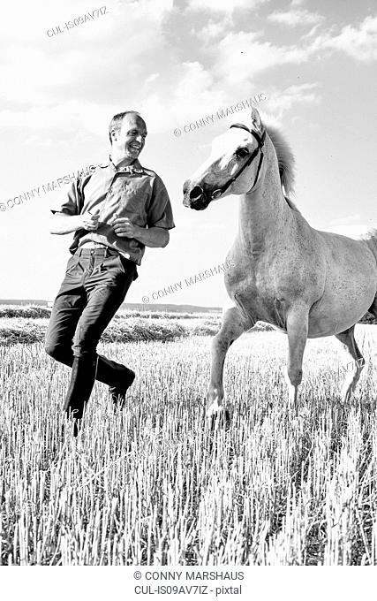 B&W image of male trainer running in front of white horse in field