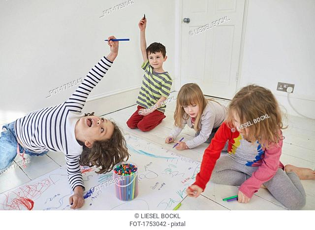 Playful children drawing on paper while sitting on floor