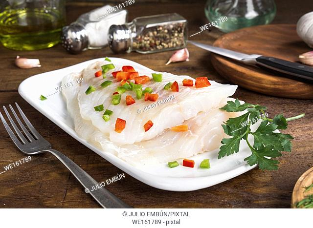 two fresh cod fillets ready to be cooked, on wood