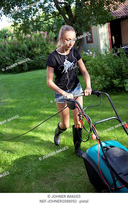 Teenage girl mowing lawn in backyard