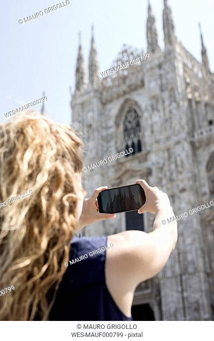 Italy, Milan, back view of tourist taking picture of cathedral with cell phone
