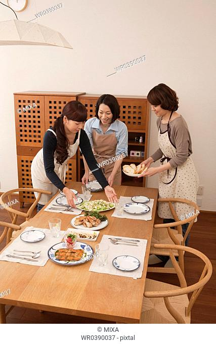 Three mid adult women serving dishes