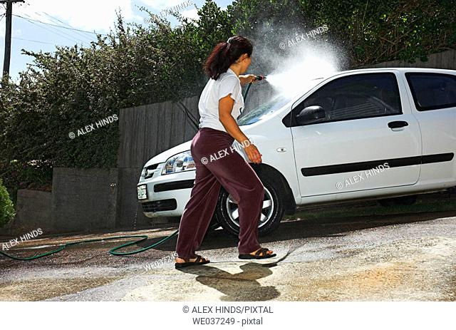 Young woman cleaning her car