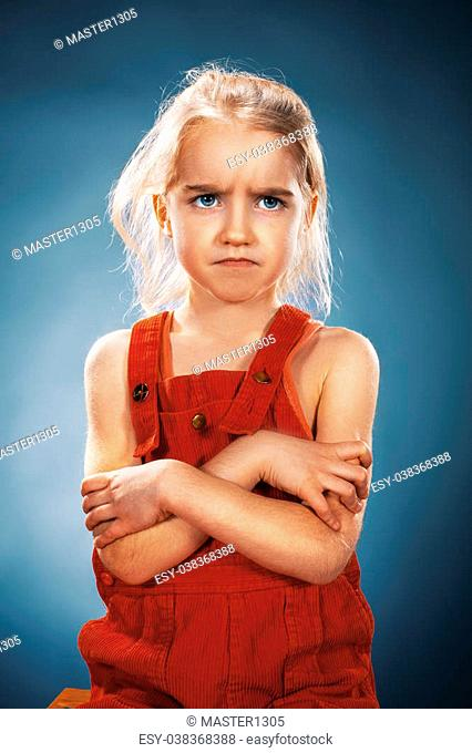 The beautiful portrait of a disaffected little girl in red dress on blue