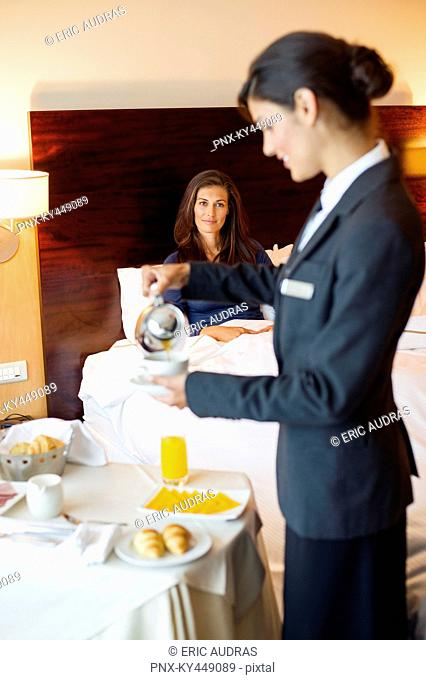 Waitress serving tea to a woman in a hotel room