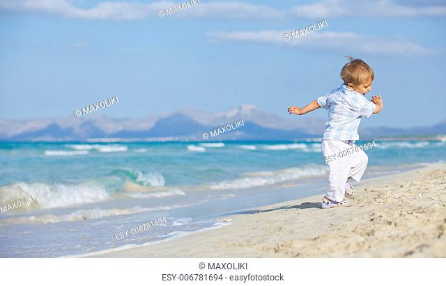 Young beautiful cute boy playing with wave at pretty beach. Majorca