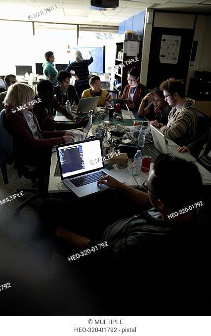 Hackers working hackathon at laptops in dark office