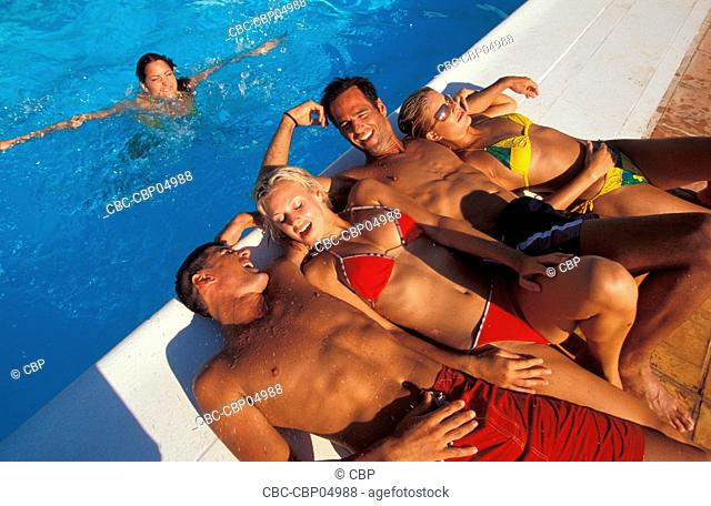Group Of Young People Lying Out By Pool