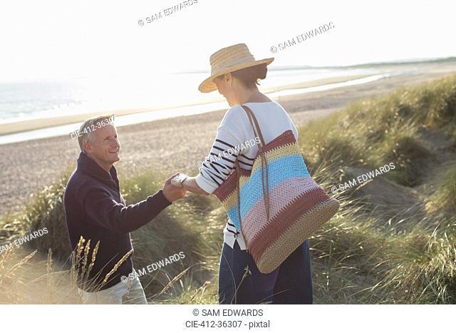 Husband helping wife on sunny beach grass path