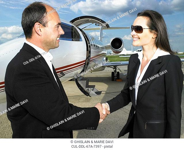 Businessman and businesswoman shaking hands in front of private jet