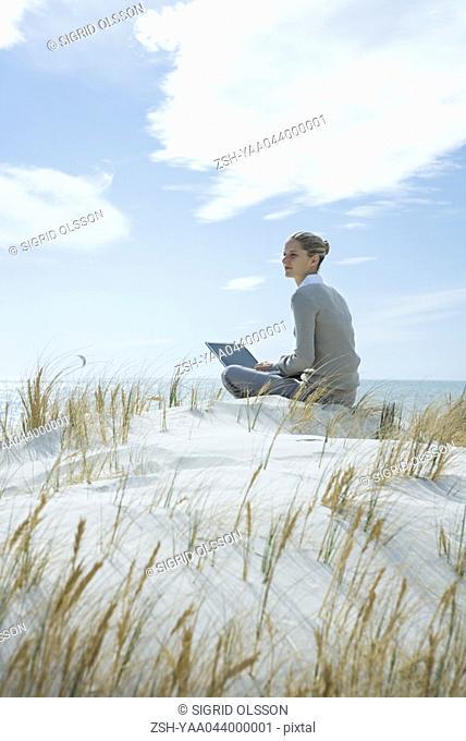 Woman sitting on dune, using laptop