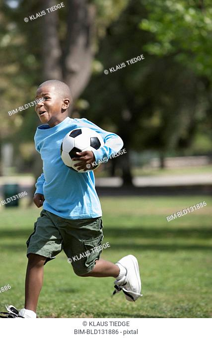 African American boy playing soccer in park
