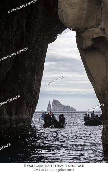 People in zodiacs exploring an arch along the coastal cliffs of San Cristobal Island (Isla San Cristobal) or Chatham Island, Galapagos Islands, Ecuador