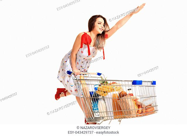 Woman with shopping cart full with products isolated over white background. A young woman rides for fun on an iron shopping basket